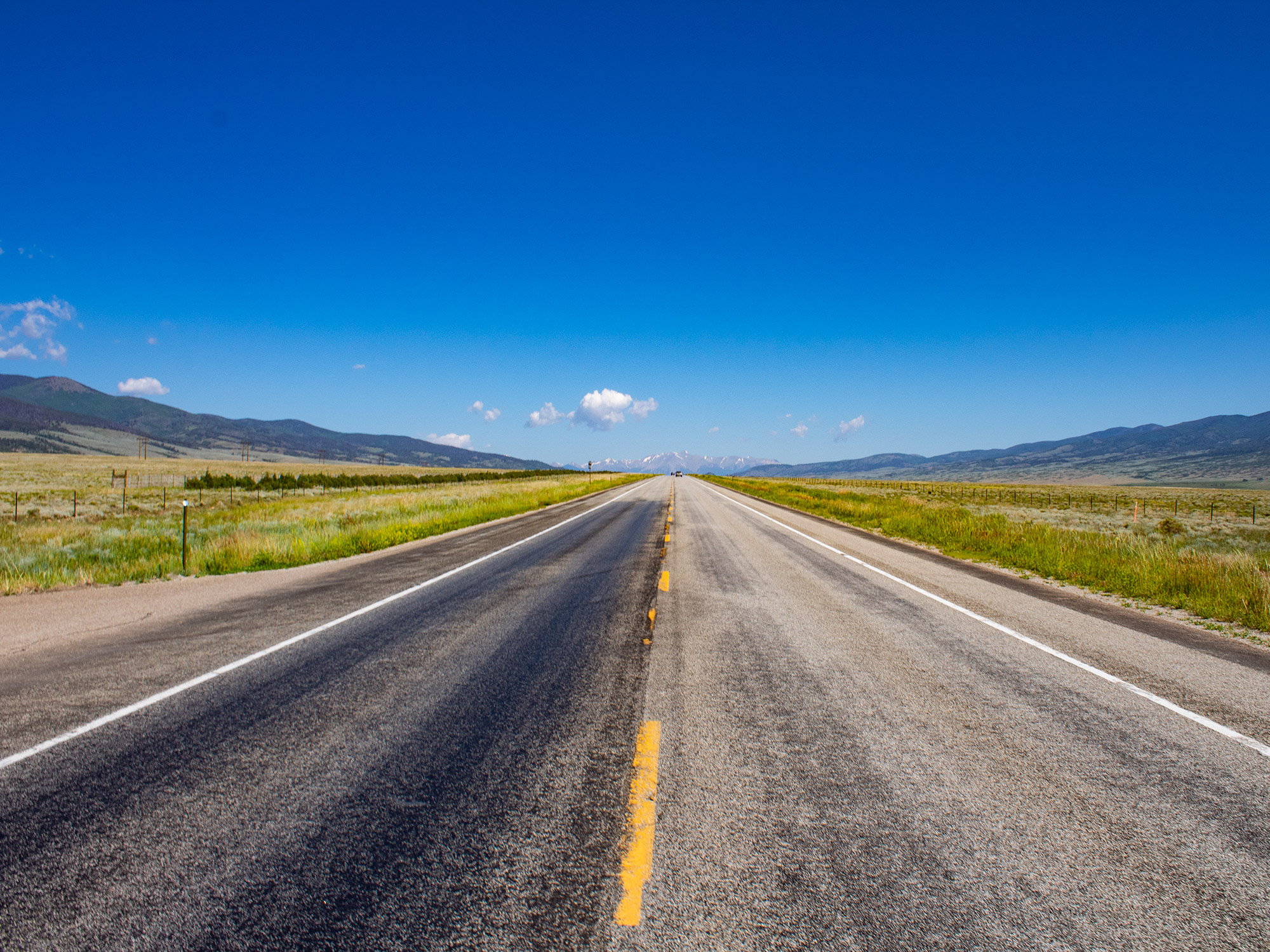An inspiring view of an open, empty road that vanishes into the mountains in Colorado