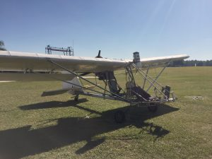 An ultralight airplane sitting in a grassy field before taking off with a hang glider