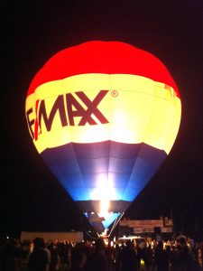A balloon glows in the dark as it fills with hot fire during an evening show in pitch black darkness
