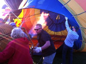 Holding open the throat of a hot air balloon as the envelope fills with hot air