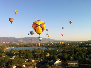 Air ballons lifting off the ground by a lake in Colorado Springs