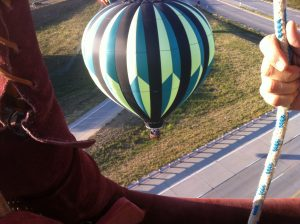 A hot air balloon prepares to land on the ground next to a highway overpass