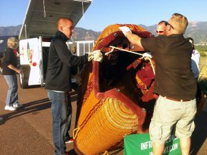 A ground crew loads up the hot air balloon basket into a trailer after flight