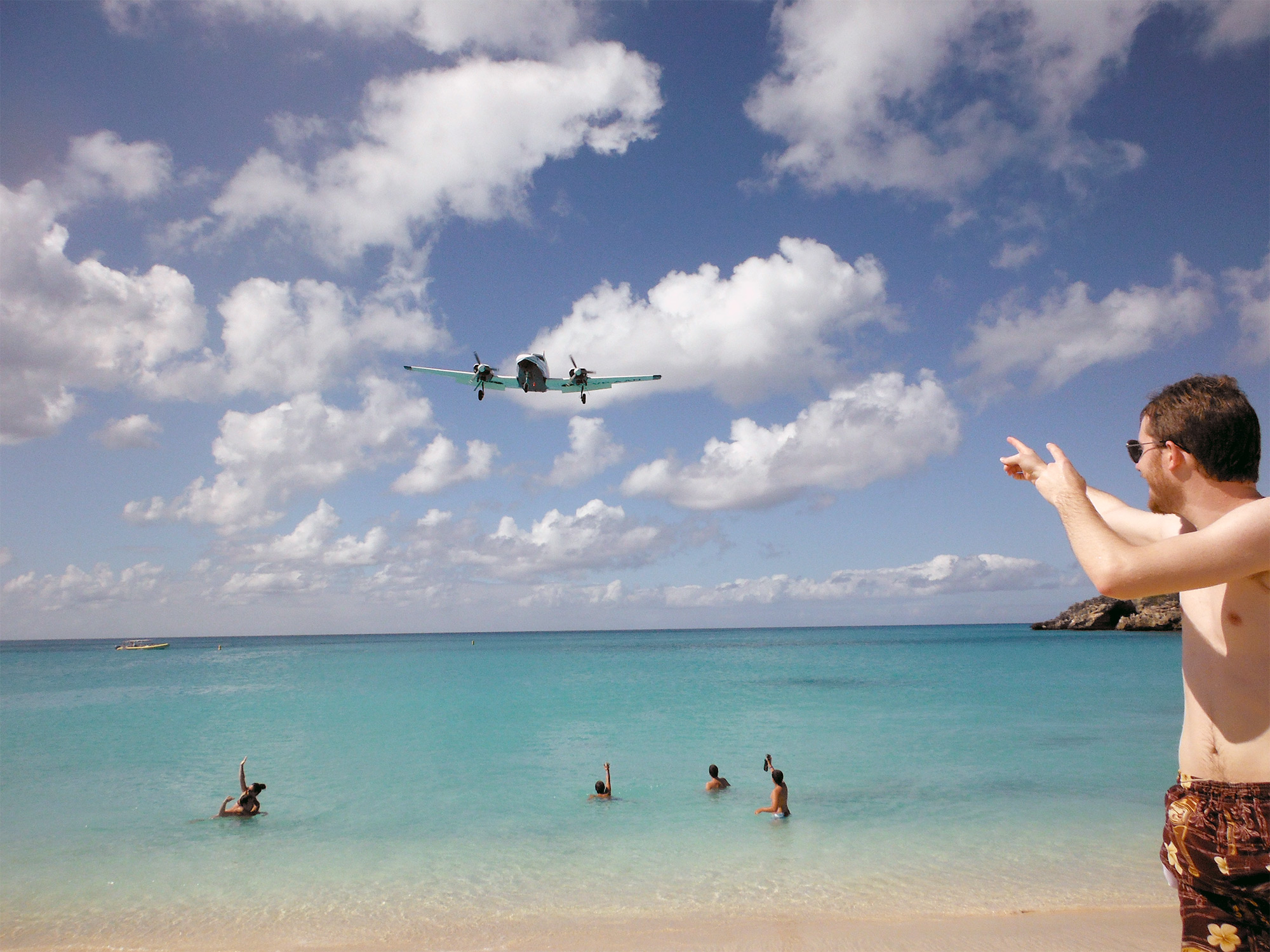 People swimming in the ocean, pointing up at an airplane flying overhead at Maho Beach in Sint Maarten
