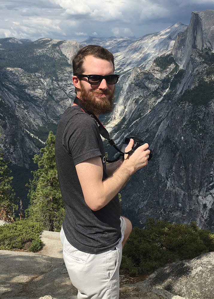 Ron Stauffer at Glacier Point in Yosemite National Park, smiling and holding a camera with Half Dome in the background