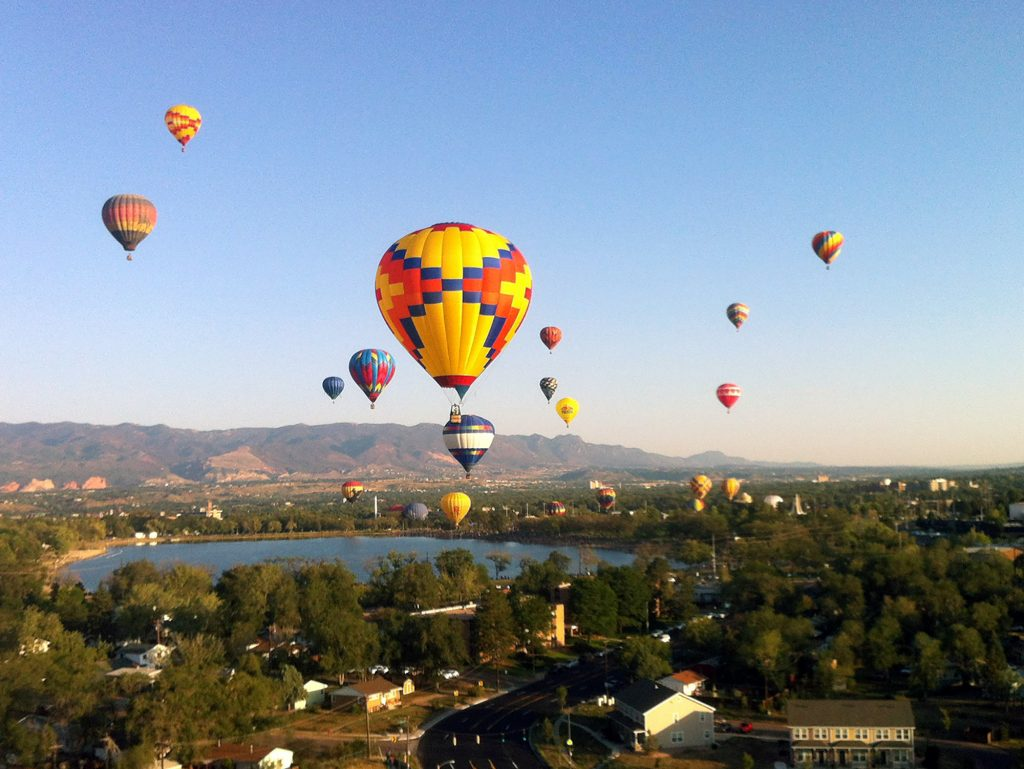 A view of hot multiple hot air balloons flying above a lake with mountians in the background
