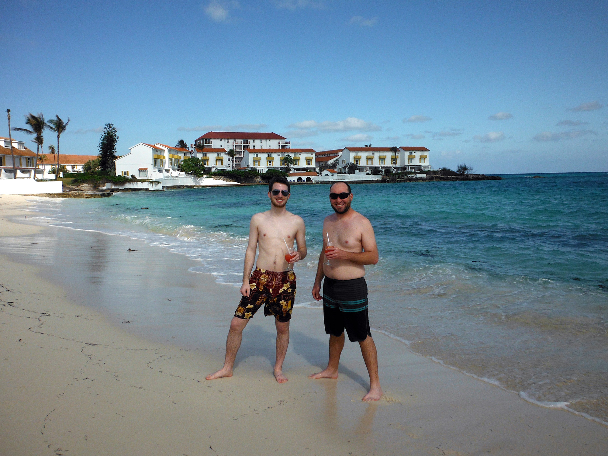 Ron Stauffer and a friend holding drinks, smiling, and standing on a beach in The Bahamas