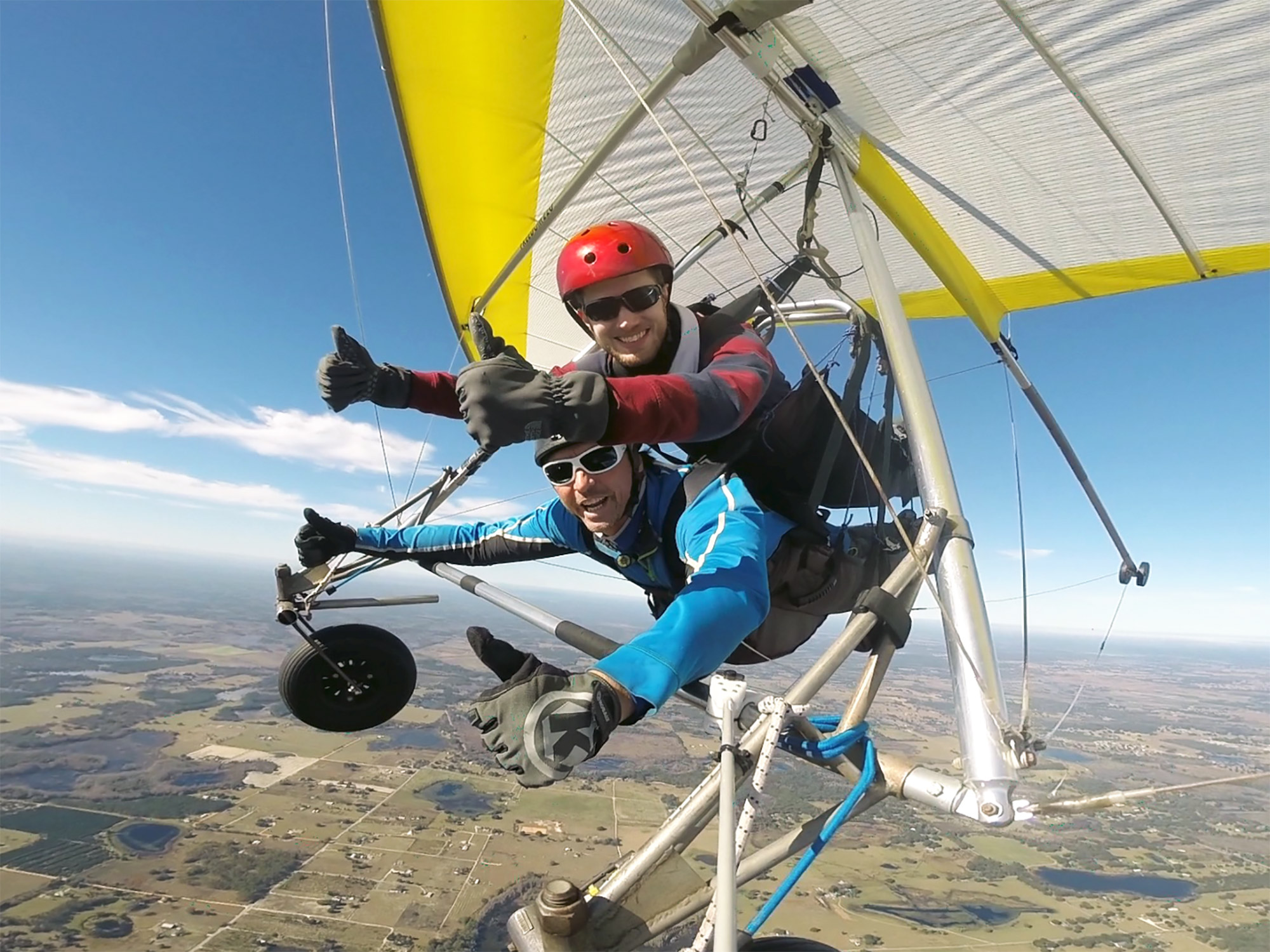 Ron Stauffer flying in a hang glider, smiling and holding two thumbs up.